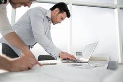两位建筑师为工作使用一台膝上型计算机 免版税图库摄影