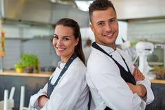 两位微笑的厨师在厨房里 库存照片