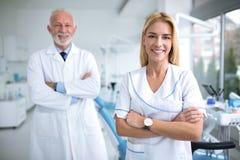 两位微笑的牙医在一个牙齿办公室 图库摄影