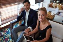 两位微笑的金融家在公司衣裳穿戴了有交涉,当坐在现代办公室内部时 免版税库存图片