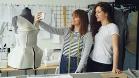 两位快乐的衣物设计师做与巧妙的电话的滑稽的selfie,当站立在穿衣的时装模特旁边时 股票视频