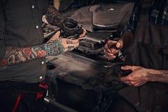 两位技工审查引擎的细节,当站立在车库时的一辆残破的汽车附近 免版税库存图片