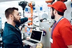 两位推销员检查tooks存货与膝上型计算机在电动工具商店 免版税库存照片