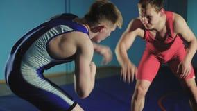 两位摔跤手希腊罗马搏斗在蓝色背景缓慢的mo 股票录像