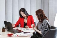 两位时髦的女孩设计师与膝上型计算机和文献一起使用在坐在书桌的项目 ?? 免版税库存照片