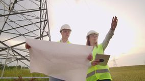 两位电工,站立在领域在电在盔甲的送电线附近 站立在 股票视频