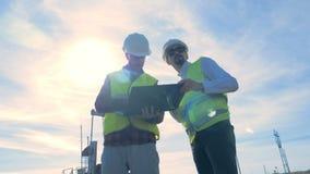 两位男性专家的运作的过程在抽油装置,油泵附近的汽油生产站点 股票录像