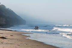 两位男性冲浪者运载冲浪板在月光国家海滩在有雾的早晨 免版税图库摄影