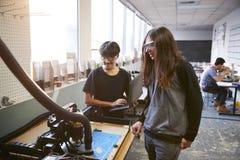 两位男性大学生在科学机器人学或工程学类的计算机控制的船具工作 免版税库存照片