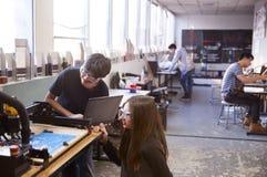 两位男性大学生在科学机器人学或工程学类的计算机控制的船具工作 免版税库存图片