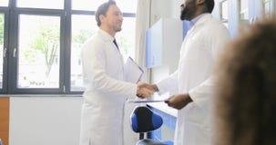 两位男性科学家握手在congradulating与成功的实验的实验室收效在繁忙的队  股票录像