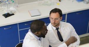 两位男性科学家谈论化学制品在试管,一起分析运作在实验室的研究的结果 股票视频