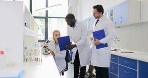 两位男性科学家谈论研究的结果与妇女与显微镜一起使用在现代实验室,队od 股票录像