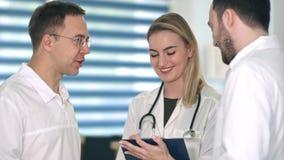 两位男性医生有讨论,当做笔记的微笑的护士在她的剪贴板时 免版税库存照片