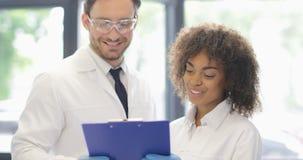两位科学家谈论文件与实验的结果,工作在实验室的现代研究员队 股票视频