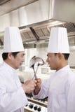 两位竞争厨师在手上对峙与厨房器物 免版税图库摄影