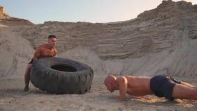 两位肌肉开放有胸腔的运动员在做俯卧撑和推挤一个巨大的轮子的海滩的主动模式下训练反对a 股票录像