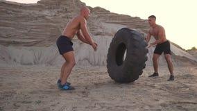 两位肌肉开放有胸腔的运动员在做俯卧撑和推挤一个巨大的轮子的海滩的主动模式下训练反对a 影视素材