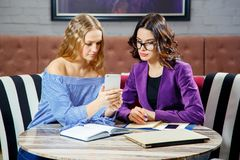 两位自由职业者在咖啡馆谈论新的项目,当坐与电子设备时 图库摄影