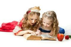 两位迷人的小公主Reading The Magic Book 免版税库存照片