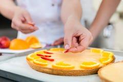 两位酥皮点心面包师被做的果子蛋糕 免版税库存照片