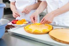 两位酥皮点心面包师被做的果子蛋糕 库存照片