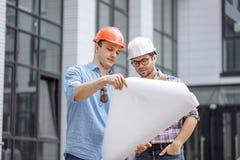 两位雄心勃勃的工程师开发拥有想法创造摩天大楼 图库摄影