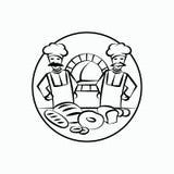 两位面包师和一张桌用面包在前景 皇族释放例证