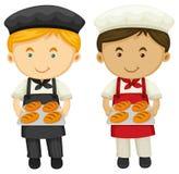 两位面包师用新鲜的被烘烤的面包 图库摄影