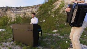 两位音乐家使用在岩石的钢琴演奏家和手风琴师在海的日落 影视素材