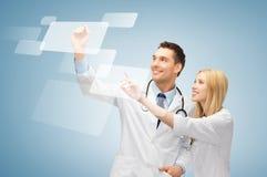 两位医生与虚屏一起使用 免版税库存照片