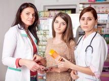 两位医生和一个客户在药房里面 库存图片