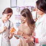 两位医生和一个客户在药房里面 免版税库存图片