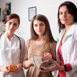 两位医生和一个客户在药房里面 免版税图库摄影