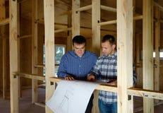 两位建造者在一个新的修造房子里 免版税库存图片