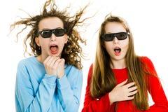 两使戏院的青少年的女孩惊奇戴3D眼镜体验5D戏院作用-风的吹入面孔 免版税库存图片