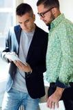 两使用数字式片剂的商人在办公室 免版税库存照片