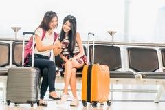 两使用智能手机检验飞行或网报到的年轻亚裔女孩,一起坐在机场等待的位子 免版税库存图片