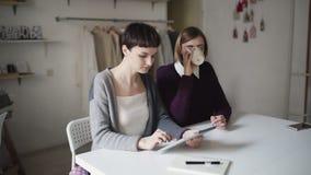 两使用片剂的创造性的妇女为在背景垂悬的衣裳的新的项目 影视素材