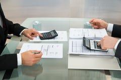 两使用计算器的商人在办公室 免版税库存图片