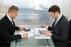 两使用计算器的商人在工作场所 免版税库存照片