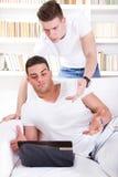 两使看膝上型计算机的青年人惊奇 免版税库存图片