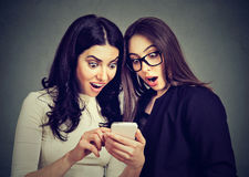 两使观看在线的妇女室友惊奇提议在一个巧妙的电话 免版税图库摄影