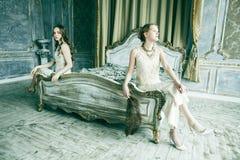 两俏丽的双一起豪华房子内部的姐妹白肤金发的卷曲发型女孩,富有的年轻人概念 免版税库存照片