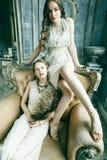 两俏丽的双一起豪华房子内部的姐妹白肤金发的卷曲发型女孩,富有的年轻人概念 免版税图库摄影