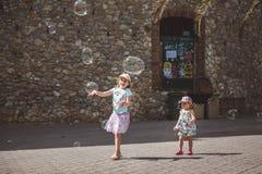 两俏丽的女孩使用与在街道的大泡影在夏日 免版税库存照片