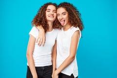 两俏丽的女孩孪生微笑,显示在蓝色背景的舌头 免版税图库摄影