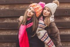两俏丽的女孩穿温暖的冬天衣裳 库存照片