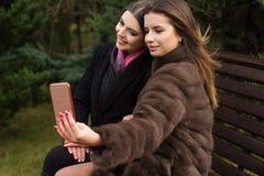两俏丽的女孩采取与智能手机的selfie 免版税库存照片