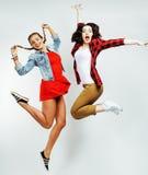 两俏丽的浅黑肤色的男人和白肤金发的跳跃愉快微笑在白色背景,生活方式人概念的十几岁的女孩朋友 免版税库存照片